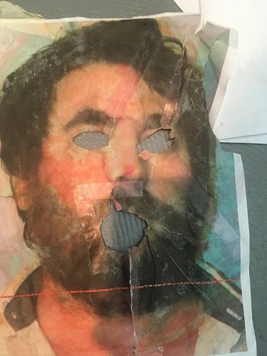 Image of picture of artist, Richard Haley's face with his eyes and mouth torn away revealing a light blue/grey fileld behind