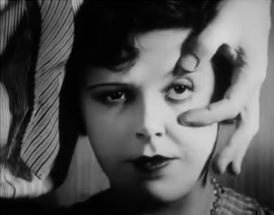 A screen shot of a man about to supposedly cut a woman's eye with a straight razor from the 1929 Un Chien Andalou movie by Salavador Dali and Luis Bunuel