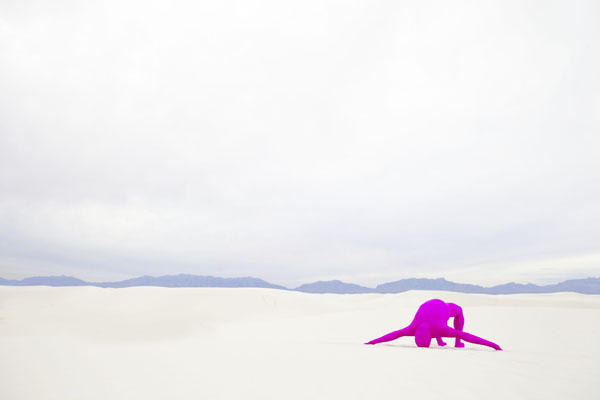 A photograph by Toban Nichols of a barren landscape with a magenta colored human form bent over backwards