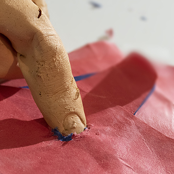This is a picture of fake human finger pressuing some wrinked red paper by Richard Haley