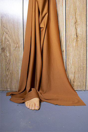This is a picture of brown cloth hanging against a wood panel wall with a fake foot sticking out at the bottom by Richard Haley