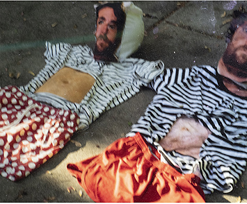 This is a picture of two simulated bodies with photo faces and clothes laid out on the ground by Richard Haley