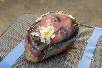 This is a picture of a mankin head with margarine in it's mouth on a cousion by Richard Haley