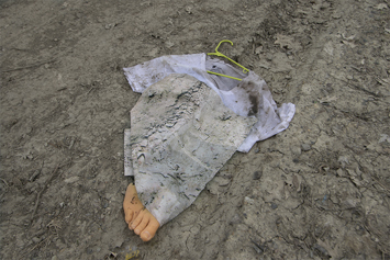 This is a picture of a lavendar dress with a yellow coat hanger with a fake foot sticking out at the bottom on the ground and has been run over by an automobile by Richard Haley